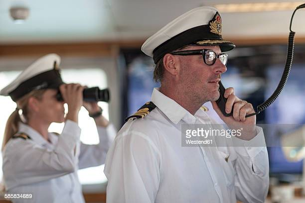 ship captain on bridge talking on radio - team captain stock pictures, royalty-free photos & images