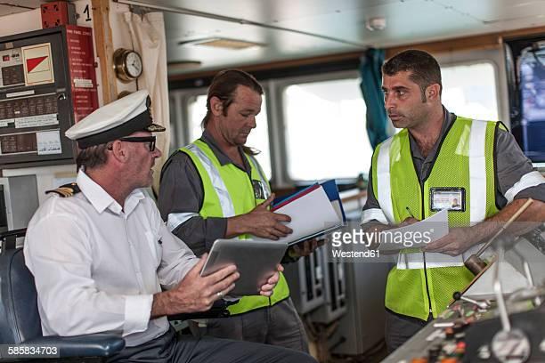 Ship crew and captain on bridge