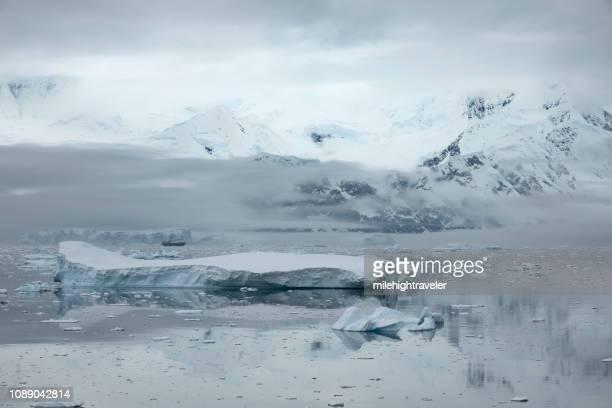 Ship cruises ice filled Neko Harbor Antarctic Peninsula mountain glaciers Antarctica