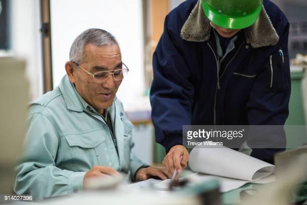 a ship designer and an engineer discuss cargo ship blueprints - オーバーオール ストックフォトと画像
