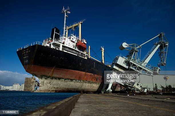 A ship hangs over the edge of the port after being washed up during the March 11 tsunami and earthquake at Sendai port in the city of Natori in...