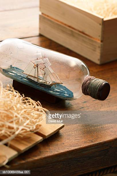 ship in bottle on table with open crate - ship in a bottle stock pictures, royalty-free photos & images