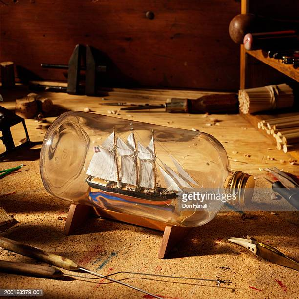 ship in bottle surrounded by hand tools, elevated view - ship in a bottle stock pictures, royalty-free photos & images
