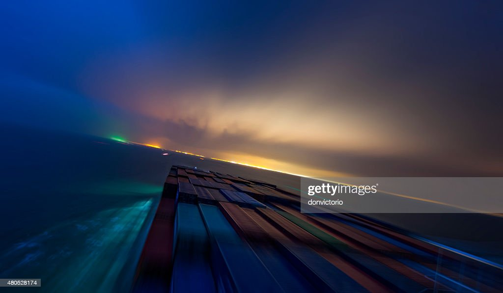 Ship in motion by night approaching the bright coast : Stock Photo
