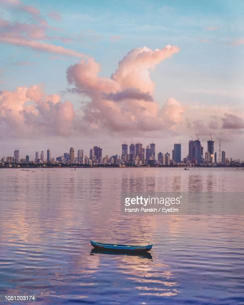 ship in sea against buildings in city - mumbai stock photos and pictures