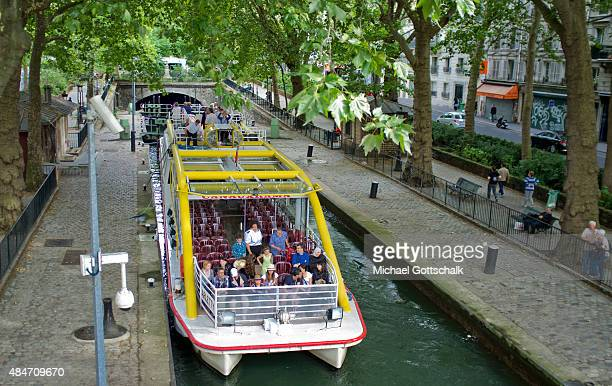 A ship lock with a Sightseeing Boat on Canal Saint Martin on July 31 2015 in Paris Frankreich