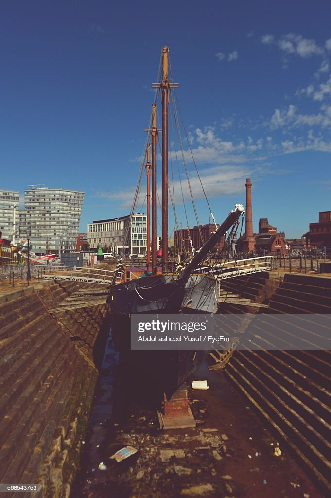 Ship Moored At Harbor Against Buildings : Stock Photo