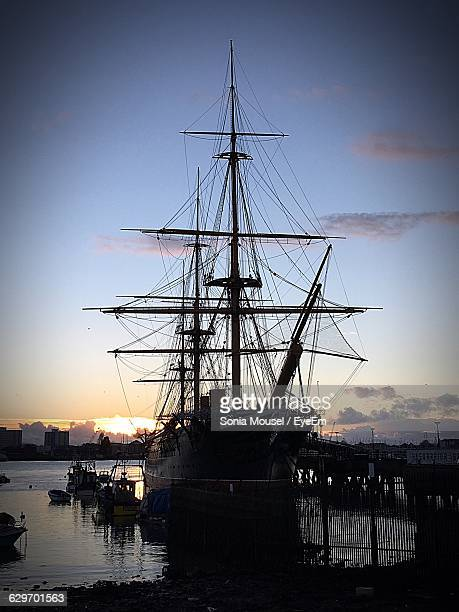 ship moored at harbor on river against sky during sunset - portsmouth england stock pictures, royalty-free photos & images