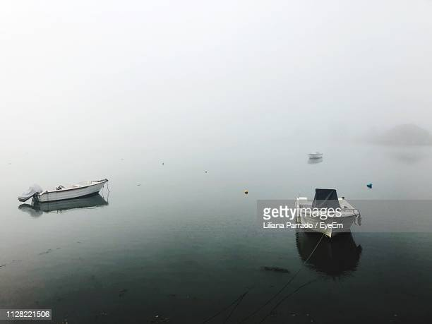 ship moored in lake against sky - moored stock pictures, royalty-free photos & images