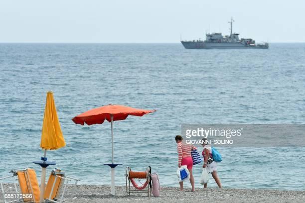 A ship of the Italian Coast Guards patrol as tourists walk along the beach near the Media Center of the G7 in the coastal town of Giardini Naxos...