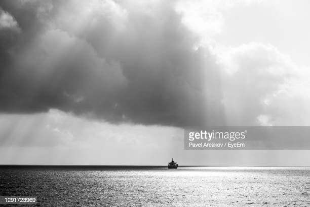 ship on the open sea in rainy weather under the sun - djibouti stock pictures, royalty-free photos & images