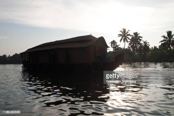 ship on vembanad lake against the sun, kerala backwaters, india - argenberg fotografías e imágenes de stock
