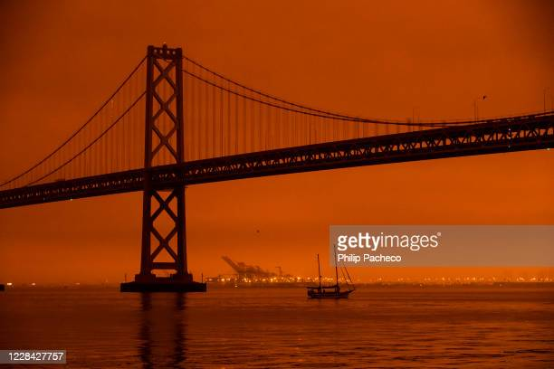Ship passes beneath the Bay Bridge as smoke from various wildfires burning across Northern California mixes with the marine layer, blanketing San...