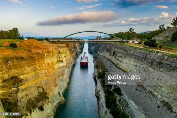 ship passing through corinth canal in greece - kanal stock-fotos und bilder