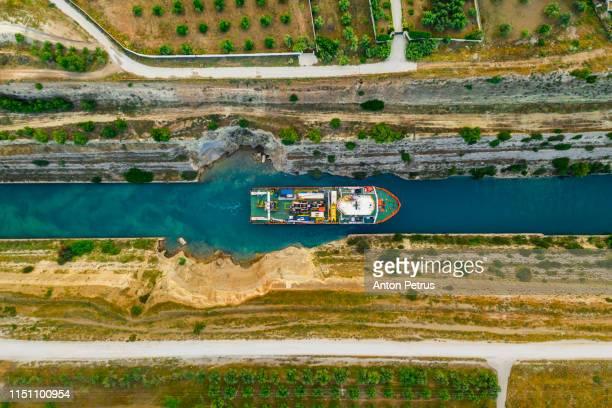 ship passing through corinth canal in greece - meerkanal stock-fotos und bilder