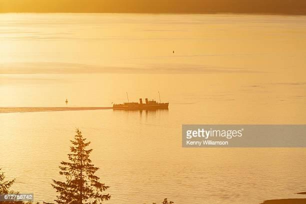 A ship sailing at sunset