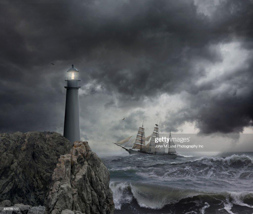 Ship Sailing Near Lighthouse On Stormy Seas Stock Photo