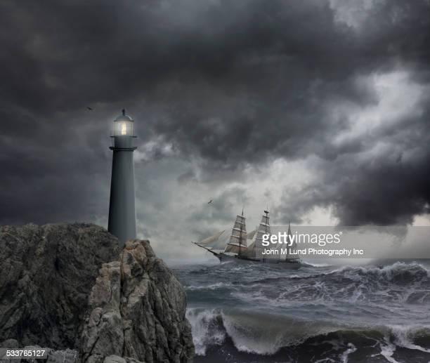 Ship sailing near lighthouse on stormy seas