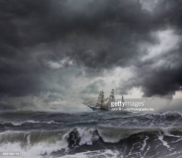 ship sailing on stormy seas - pirate ship stock photos and pictures