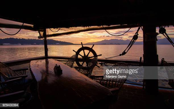 Ship scene in sunset with wooden steering wheel