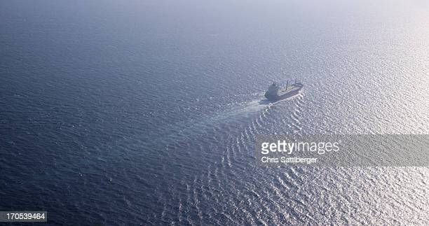ship steaming across ocean into the sun - seascape stock pictures, royalty-free photos & images