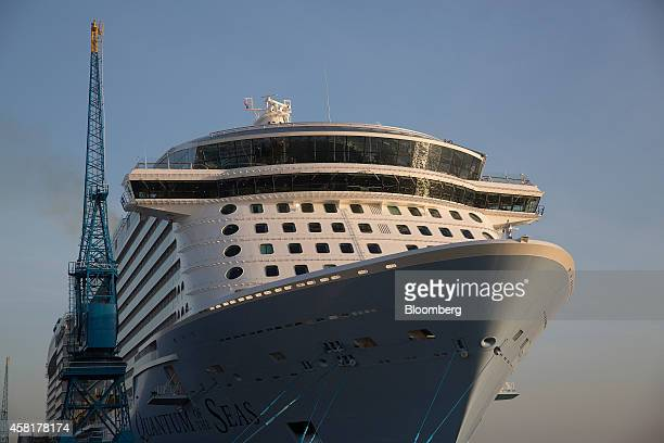 A ship to shore crane stands alongside the Quantum of the Seas cruise ship operated by Royal Caribbean Cruises Ltd as it sits moored to a berth at...