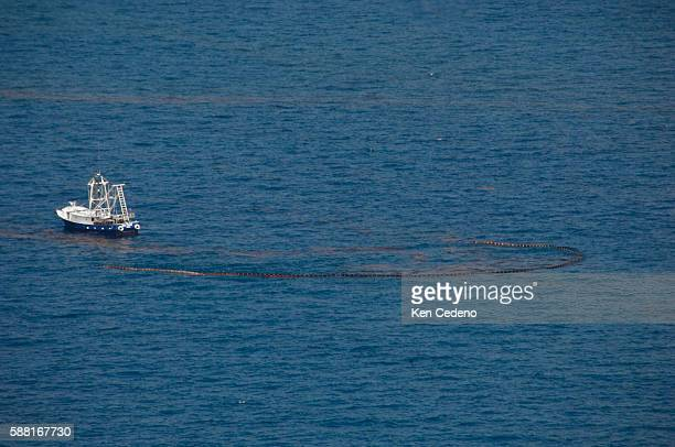 A ship using booms circles and contains oil from the site of the BP Deepwater Horizon oil spill in the Gulf of Mexico Sunday July 11 2010 BP is...