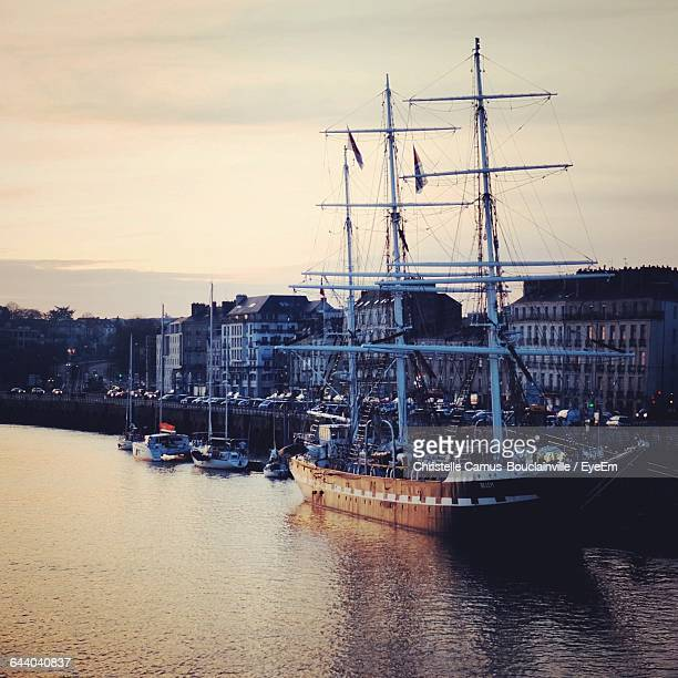 ship with sailboats moored in river at city against sky during sunset - loire atlantique photos et images de collection