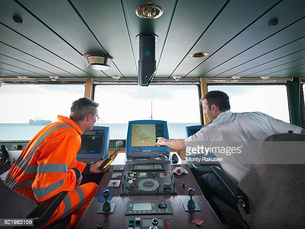 Ship worker and captain inspecting radar on ship at sea