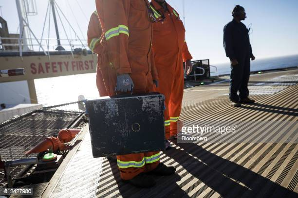 A ship worker prepares to board a helicopter carrying a case of diamonds sourced from the seabed to onshore vaults aboard the Mafuta diamond mining...