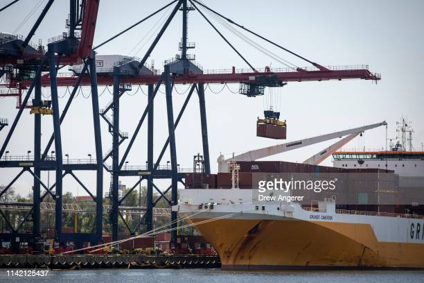 A shipping container is loaded onto a cargo ship at the New York Container Terminal in Staten Island as seen from Elizabeth New Jersey May 7 2019 US...