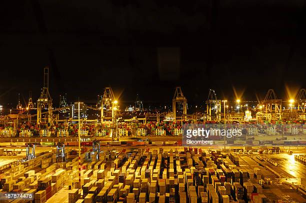 Shipping containers and gantry cranes stand illuminated at night in the Port of Rotterdam seen from the Maersk McKinney Moeller TripleE Class...