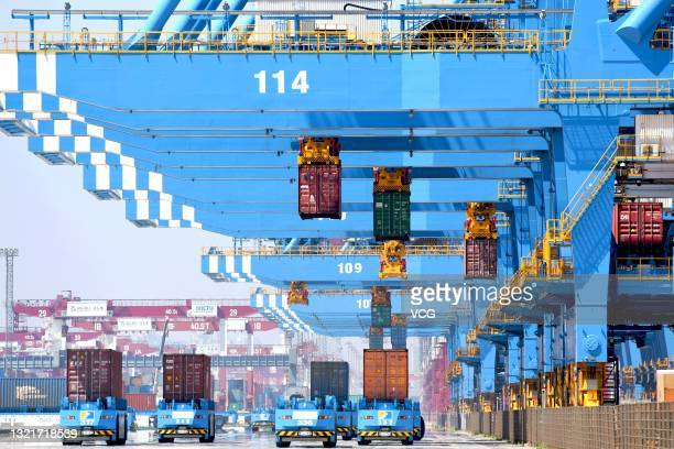 Shipping containers are loaded onto unmanned vehicles at Asia's first fully automated container terminal of Qingdao Port on June 4, 2021 in Qingdao,...