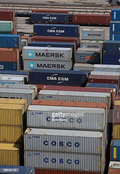 Shipping containers branded with CMA CGM SA AP MoellerMaersk A/S and China Ocean Shipping Group Co logos stand on the dockside at the port of Koper...