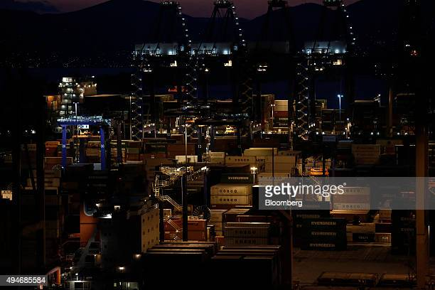Shipping containers branded with the logos of COSCO Pacific Ltd and Evergreen Marine Corp Taiwan Ltd sit illuminated at night at the container...