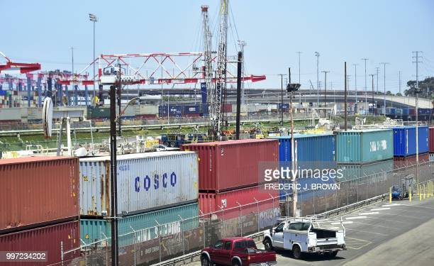 Shipping containers including those from COSCO a Chinese stateowned shipping and logistics company await transportation on a rail line at the Port of...