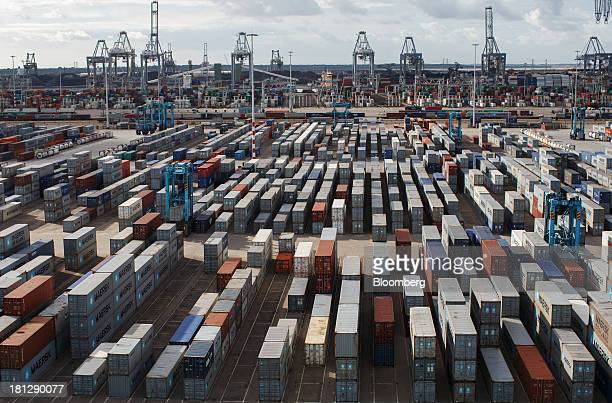 Shipping containers sit at the APM Terminal operated by AP MoellerMaersk A/S as cranes stand beyond at the Port of Rotterdam in Rotterdam Netherlands...