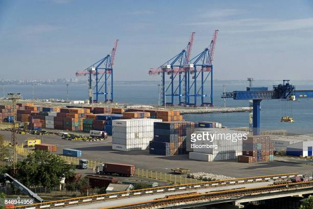 Shipping containers sit on a dockside storage area near shiptoshore cranes at Odessa central port in Odessa Ukraine on Wednesday Sept 13 2017 A...