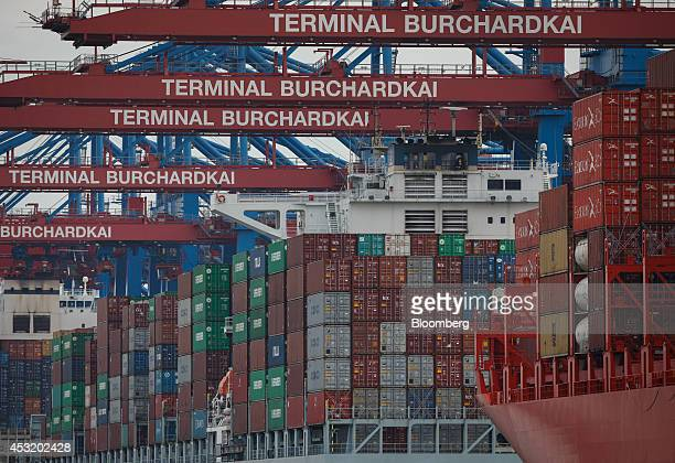 Shipping containers sit on cargo vessels beneath shiptoshore cranes at the HHLA Container Terminal Burchardkai in the Port of Hamburg in Hamburg...