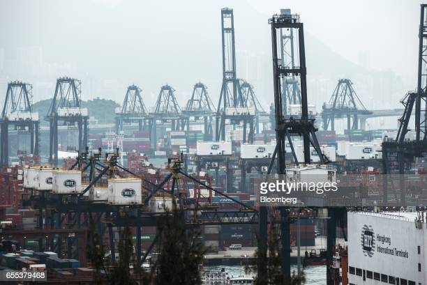 Shipping containers sit stacked among gantry canes at the Kwai Tsing Container Terminals operated by Hong Kong International Terminal a unit of CK...