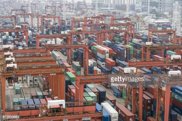 Shipping containers sit stacked among remotecontrolled gantry cranes in Container Terminal 9 operated by Hong Kong International Terminal a unit of...