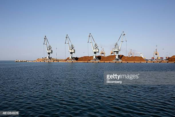 Shipping cranes stand beside supplies of unprocessed nickel ore on the dockside at Thessaloniki port operated by Thessaloniki Port Authority SA in...