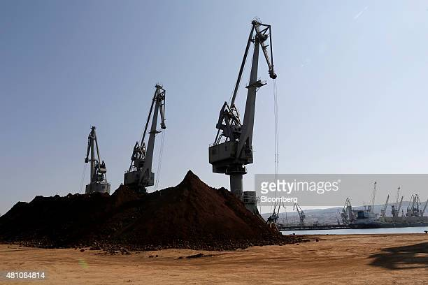 Shipping cranes stand next to supplies of unprocessed nickel ore on the dockside at Thessaloniki port operated by Thessaloniki Port Authority SA in...