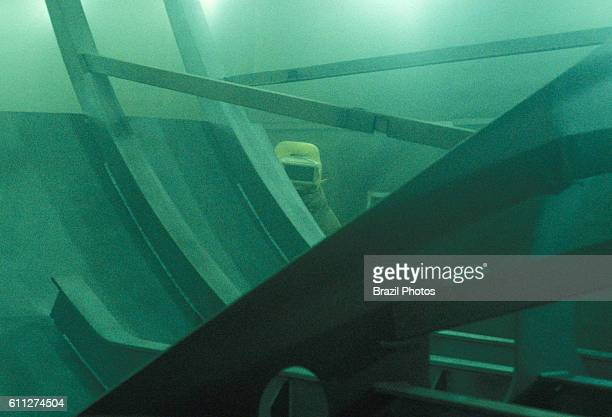 Shipping Industry in Brazil blue collar worker uses personal protective equipment in industrial process of submarine construction sandblasting a kind...
