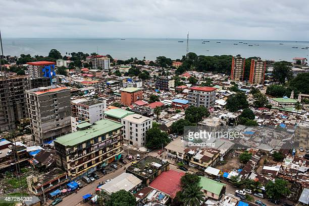 Shipping vessels sit on the waterway beyond commercial and residential buildings on the city skyline in Conakry Guinea on Saturday Sept 5 2015 While...