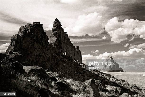 shiprock landscape, rocky coastline, black and white - shiprock stock photos and pictures