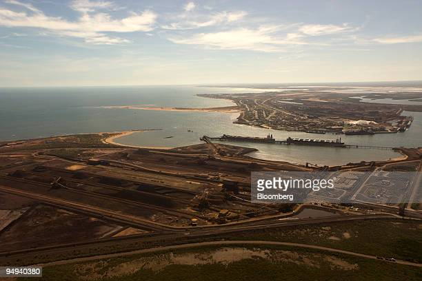 Ships are loaded with iron ore at BHP Billiton Ltd's iron ore loading facility bottom of photo on Finucane Island in Port Hedland Australia on...