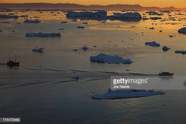 Ships are seen among the icebergs that broke off from the Jakobshavn Glacier as the sun reaches its lowest point of the day on July 23, 2013 in...