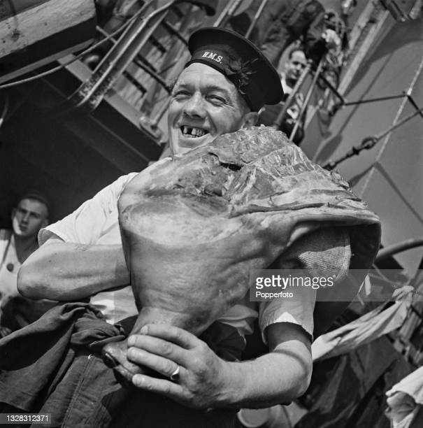 Ship's butcher carries a side of bacon to the galley aboard the Royal Navy W-class destroyer HMS Whitshed on convoy escort duty off the English coast...