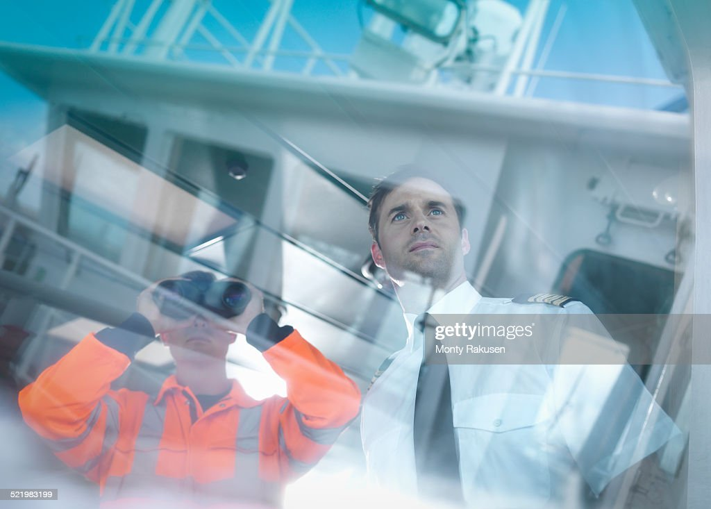 Ships captain and worker seen through reflections on container ship : Stock Photo